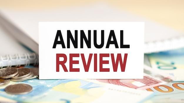 Koncepcja finansów i ekonomii. na stole rachunki, monety i biały papier, na którym jest napisany - przegląd roczny