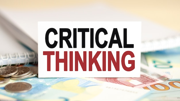 Koncepcja finansów i ekonomii. na stole są banknoty, monety i tabliczka z białej kartki, na której jest napisane – krytyczne myślenie