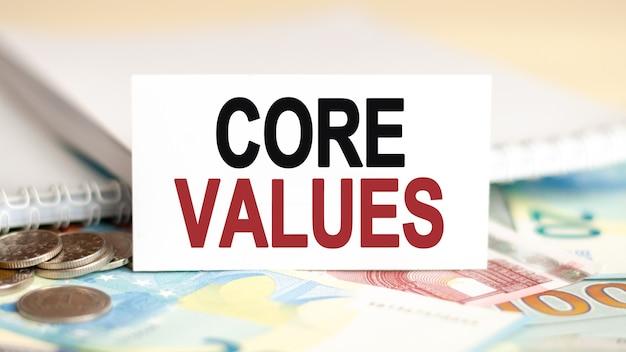 Koncepcja finansów i ekonomii. na stole są banknoty, monety i tabliczka z białej księgi, na której jest napisane - wartości podstawowe