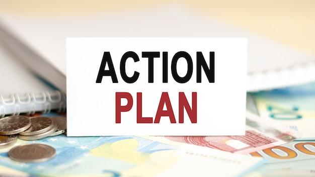 Koncepcja finansów i ekonomii. na stole są rachunki, monety i biały papier, na którym jest napisany - plan działania