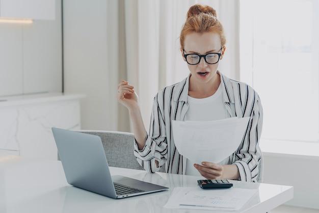 Koncepcja finansów oszczędnościowych zszokowana ruda kobieta skupiona na badaniu dokumentów rachunki czyta papier bankowy