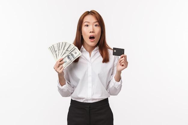 Koncepcja finansów, pieniędzy i zakupów. podekscytowana i zszokowana młoda azjatycka kobieta trzyma dolary i kartę kredytową, nerwowo patrzy w kamerę, chce marnować pieniądze na wakacje, podejmuje decyzję,