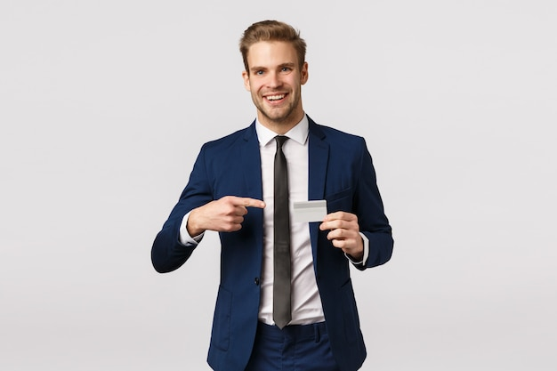 Koncepcja finansów, przedsiębiorcy i biznesu. przystojny rozochocony młody biznesmen konsultuje partnera o nowym banku, trzymający kredytową kartę, wskazujący mnie i poleca, biały tło