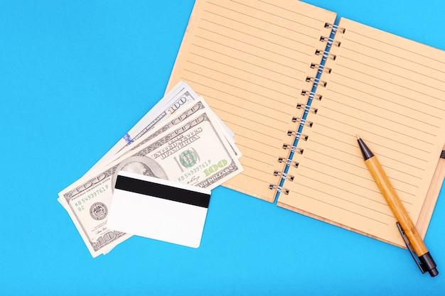 Koncepcja finansowa. na otwartym pustym notatniku są dolary, karta kredytowa i długopis na niebieskim tle, widok z góry, kopia przestrzeń. może być używany w tle, układ