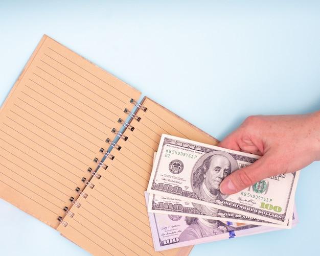 Koncepcja finansowa. ręka trzyma dolarów nad otwartym pustym notatnikiem do pisania, zbliżenie, widok z góry, kopia przestrzeń. może być używany w tle, układ
