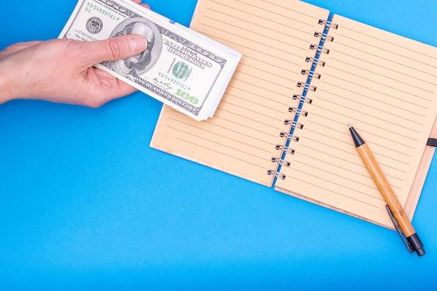 Koncepcja finansowa. ręka trzyma dolarów nad otwartym pustym notatnikiem i długopisem, zbliżenie, widok z góry, kopia przestrzeń. może być używany w tle, układ