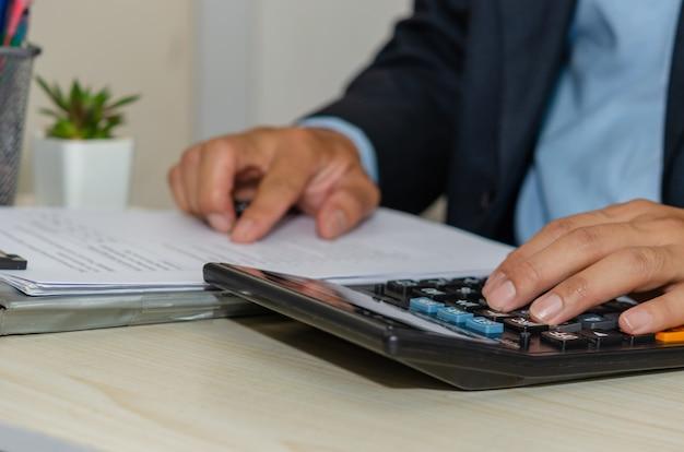 Koncepcja finansowania inwestycji biznesowych. biznesmen za pomocą raportu z badania rynku rachunkowości kalkulatora. praca w domu.