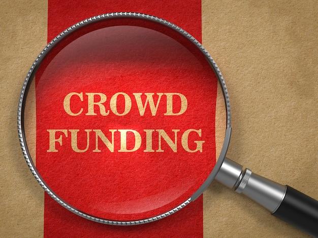 Koncepcja finansowania tłumu. lupa na starym papierze z czerwoną linią pionową.