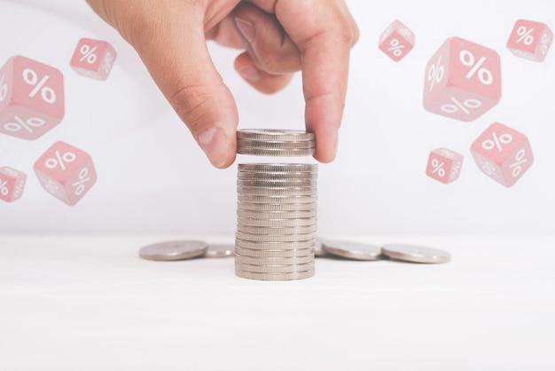 Koncepcja finansowych i oszczędności stopy procentowej. ręczne wkładanie monet do stosu z monetami i symbolem procentu.
