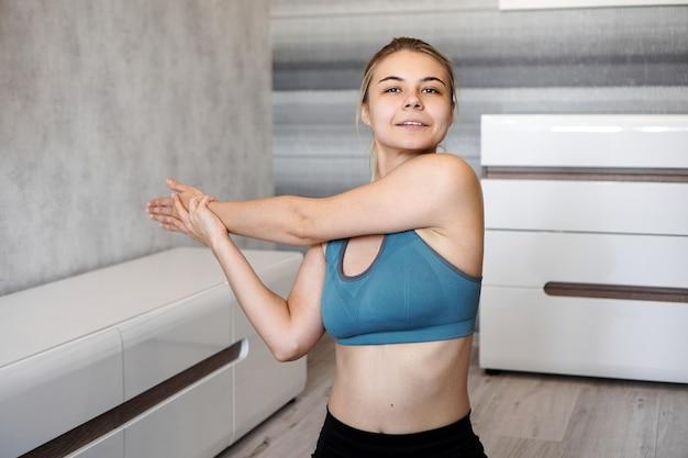 Koncepcja fitness, domu i diety. uśmiechnięta dziewczyna streching na podłodze w domu