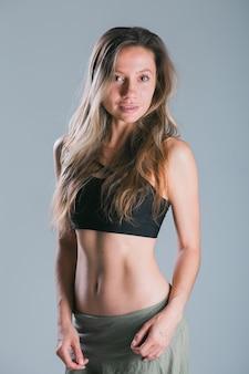 Koncepcja fitness i diety portret młodej kobiety z idealnym sportowym ciałem i dość płaskim abs w