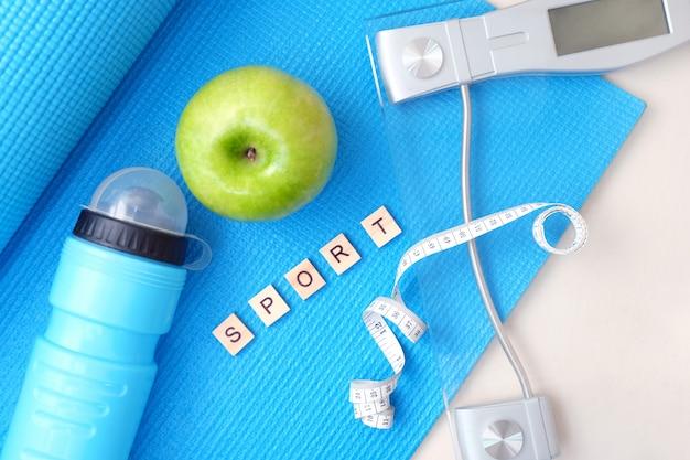 Koncepcja fitness i sportu. mata do jogi, łuski, zielone jabłko