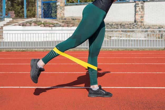 Koncepcja fitness i sportu, trening na świeżym powietrzu. kobiece nogi ćwiczą za pomocą gumki fitness na czerwonym torze.