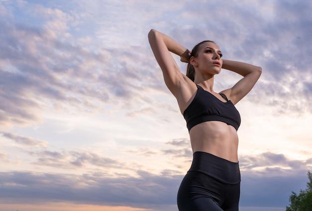 Koncepcja fitness i styl życia - kobieta uprawia sporty na świeżym powietrzu na plaży