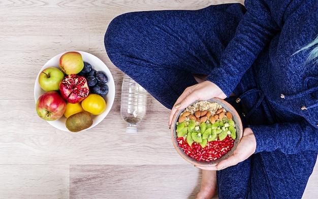Koncepcja fitness i zdrowego stylu życia. kobieta odpoczywa i po treningu spożywa zdrowe płatki owsiane. widok z góry.