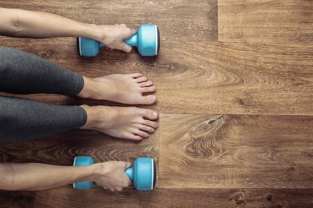 Koncepcja fitness. kobiece nogi w legginsach i boso siedzi na podłodze z hantlami.