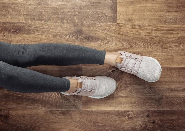 Koncepcja fitness. kobiece nogi w legginsach i butach sportowych siedzi na podłodze w pokoju.