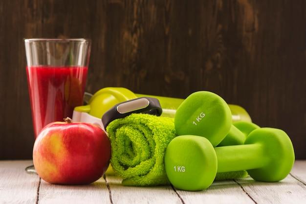 Koncepcja fitness lub dieta: hantle, świeży czerwony koktajl, jabłko