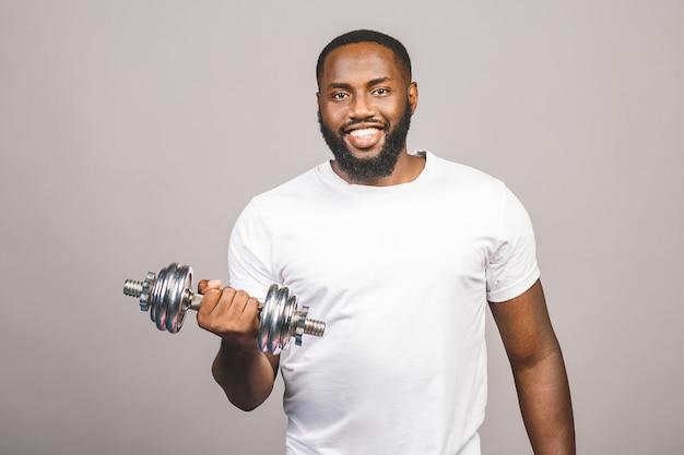 Koncepcja fitness. portret szczęśliwy amerykanina afrykańskiego pochodzenia murzyn z dumbbells odizolowywającymi nad szarym tłem.
