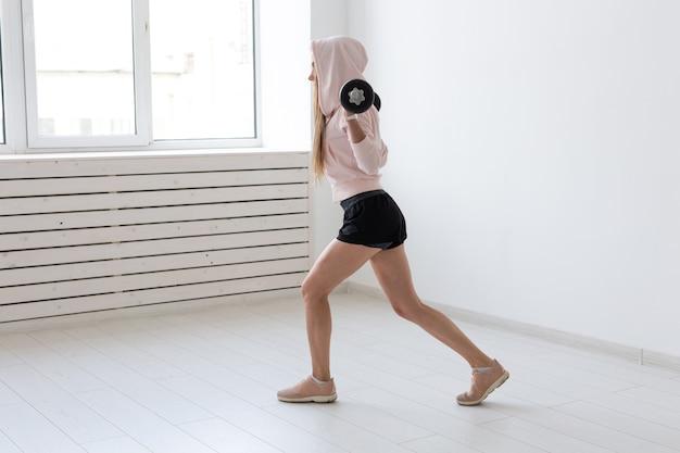 Koncepcja fitness, sport i ludzie - uśmiechnięta kobieta sportowy ze sztangą robi podzielone przysiady lub wypady.
