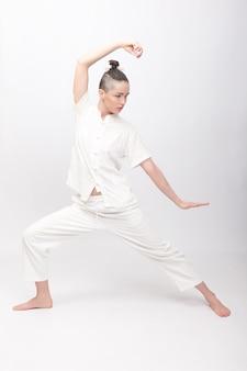 Koncepcja fitness, sport, szkolenia i styl życia - młoda kobieta robi ćwiczenia jogi. młoda kobieta ćwiczy tai chi chuan na siłowni. energia qi chińskich umiejętności zarządzania.