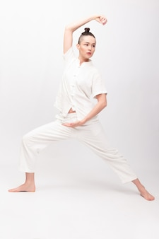 Koncepcja fitness, sport, szkolenia i styl życia - młoda kobieta robi ćwiczenia jogi. młoda kobieta praktykuje tai chi chuan na siłowni. chińska umiejętność zarządzania energią qi.