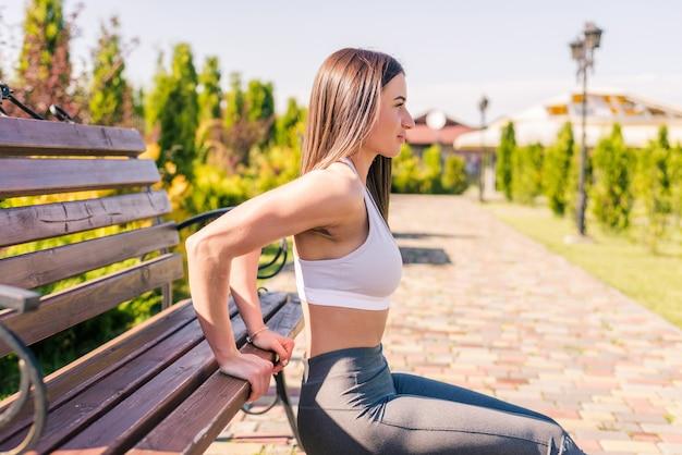 Koncepcja fitness, sport, szkolenia, park i styl życia. młoda uśmiechnięta kobieta robi pompki na ławce na świeżym powietrzu