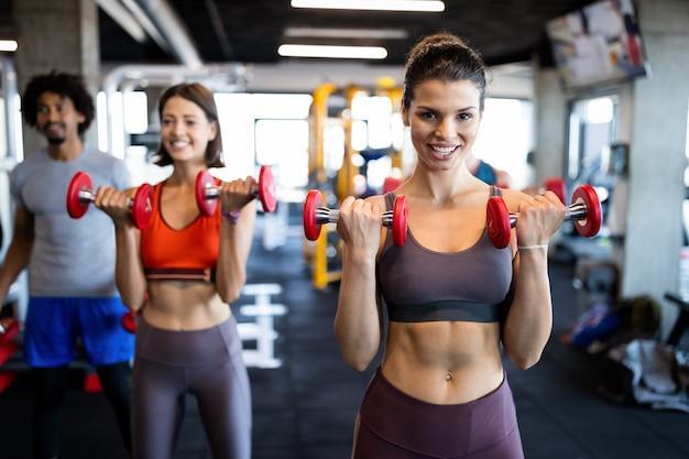 Koncepcja fitness, sport, trening i styl życia. grupa sprawnych osób ćwiczących w siłowni