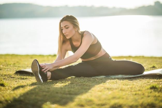 Koncepcja fitness, sportu i zdrowego stylu życia - uśmiechnięta kobieta siedzi na macie do ćwiczeń w parku miejskim latem