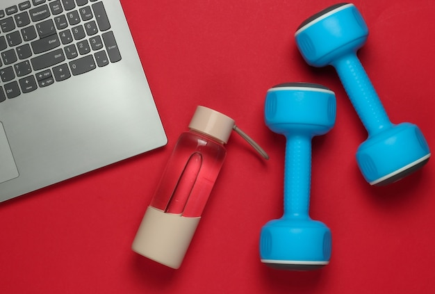 Koncepcja fitness. szkolenie online dla zawodu trenera. laptop, hantle, butelka wody na czerwonym tle. widok z góry