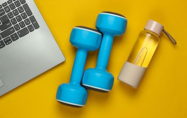Koncepcja fitness. szkolenie online dla zawodu trenera. laptop, hantle, butelka wody na żółtym tle. widok z góry