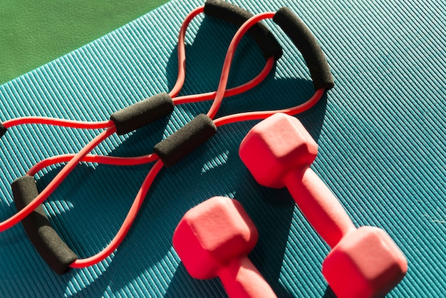 Koncepcja fitness z ekspandera i dwa hantle w klubie fitness