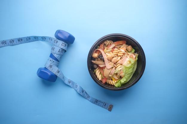 Koncepcja fitness z hantlami świeżych warzyw i taśmą pomiarową na niebiesko