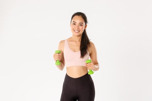 Koncepcja fitness, zdrowego stylu życia i dobrego samopoczucia. portret szczęśliwej szczupłej i silnej azjatyckiej atlety, sportsmenki w odzieży sportowej trzymającej hantle do treningu, ćwiczenia na siłowni, biała ściana