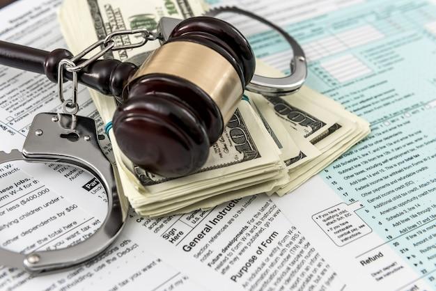 Koncepcja formularza podatkowego nas pieniądze z kajdankami młotek leżący na podatku federalnym