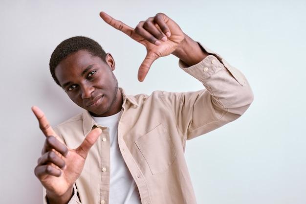 Koncepcja fotografii. afrykański mężczyzna co kwadratowy kształt z rąk, robienie zdjęć. pojedyncze białe studio ściany