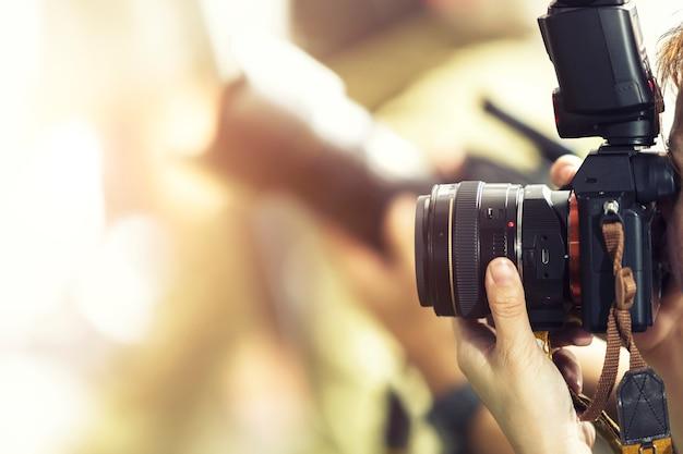Koncepcja fotografii. fotograf strzelający plenerowy z zamazanym tłem.