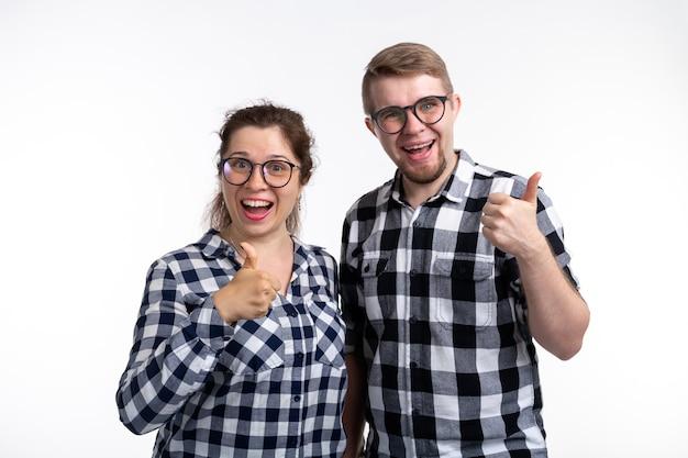 Koncepcja frajerów, maniaków, okularów i zabawnych ludzi. kilku nerdów w okularach pokazuje nam kciuki do góry