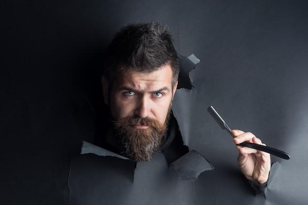 Koncepcja fryzjera poważny brodaty mężczyzna trzyma brzytwę i patrząc przez papierowy brodaty mężczyzna wygląda