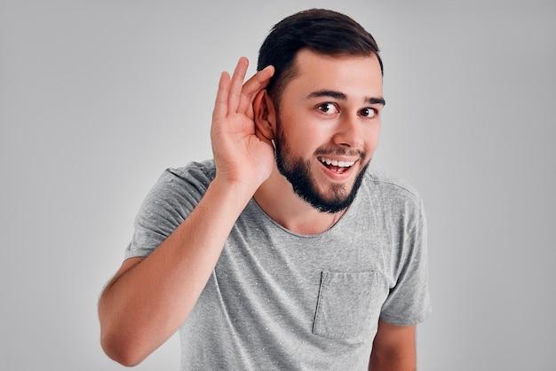 Koncepcja gestów i ludzi - młody uroczy mężczyzna ma problem ze słuchem, słuchając czegoś