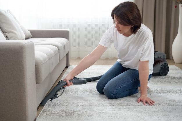 Koncepcja gospodarstwa domowego i prac domowych - szczęśliwa kobieta lub gospodyni domowa z odkurzaczem, czyszczenie podłogi pod kanapą w domu