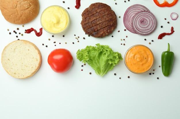 Koncepcja gotowania burgera na białym tle, widok z góry