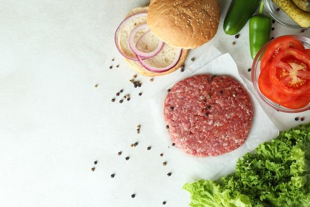 Koncepcja gotowania burgera na białym tle z teksturą