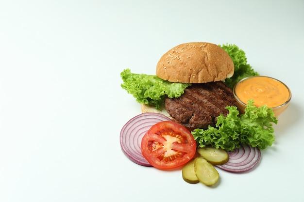 Koncepcja gotowania burgera na białym tle