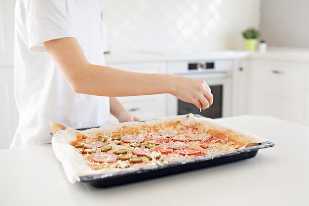 Koncepcja gotowania - gotuj ręcznie dodając tarty ser do pizzy w domowej kuchni. zbliżenie