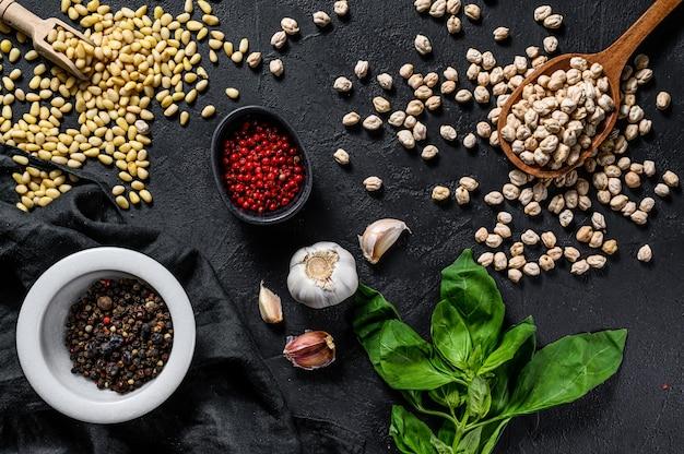 Koncepcja gotowania humusu. składniki: czosnek, ciecierzyca, orzeszki piniowe, bazylia, pieprz. widok z góry.