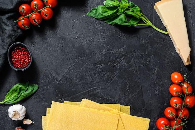 Koncepcja gotowania lasagny. składniki, prześcieradła lasagna, bazylia, pomidory koktajlowe, parmezan, czosnek, pieprz. czarne tło. widok z góry. miejsce na tekst