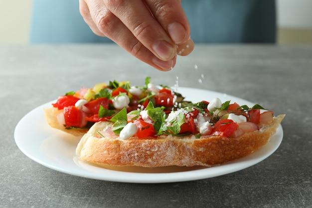 Koncepcja gotowania przekąsek bruschetta na szarym teksturowanym stole