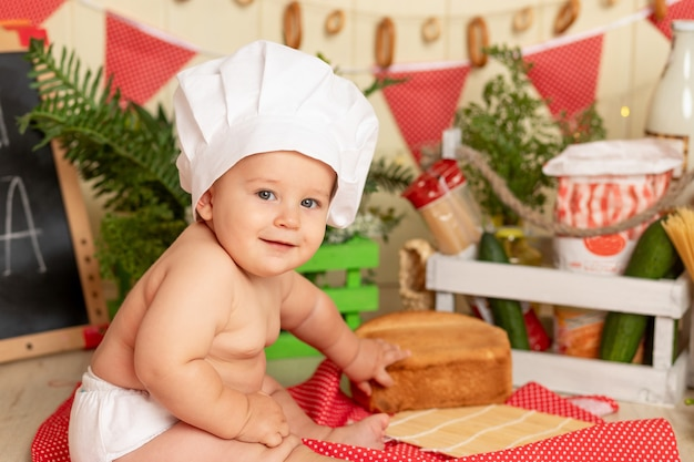 Koncepcja gotowania, szczęśliwe małe dziecko w kapeluszu szefa kuchni siedzi w kuchni z chlebem