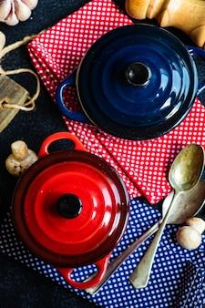 Koncepcja gotowania zupy grzybowej z ceramicznymi patelniami na ciemnym betonie